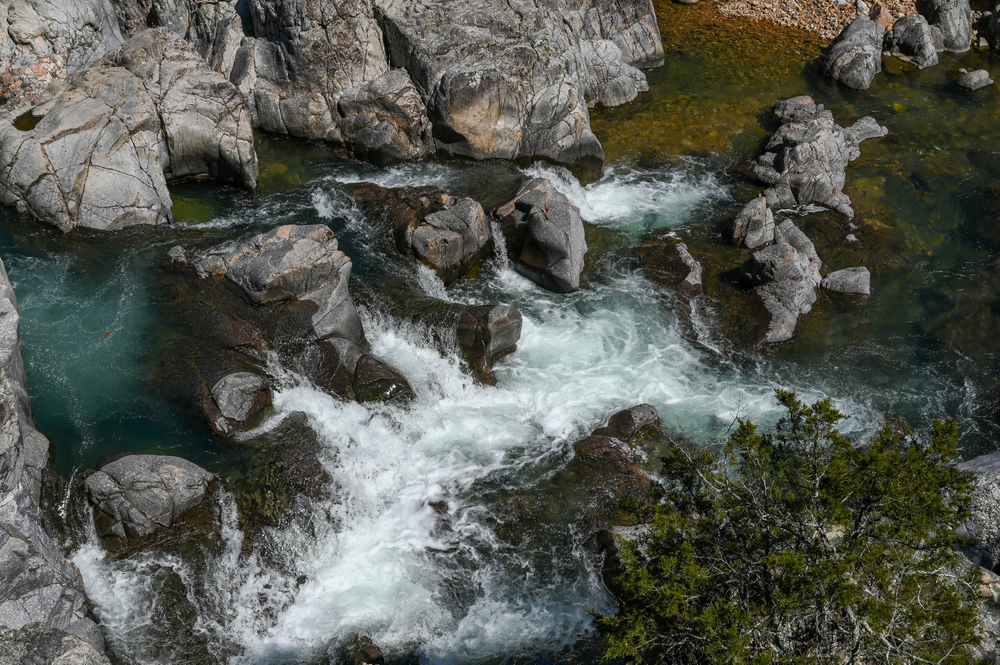 An aerial view of the Johnson Shut-ins a set of rocky waterfalls that create a pool of water. The rocks are grey and the water is fairly clear. It is one of the best Missouri road trips stops.