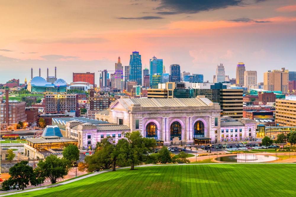 The Kansas City skyline at sunset. The city is lit up but the sky is still very bright. There is a mix of modern and old buildings in the skyline.