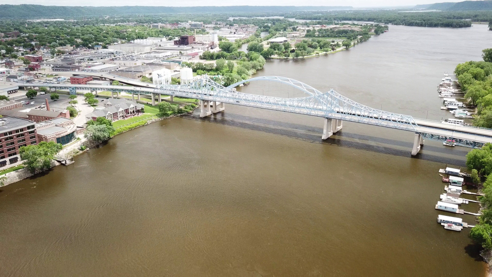 An aerial view of a large white bridge crossing the river over to LaCrosse Wisconsin. On the banks of the river you can see some house boats. On the other side of the river are lots of industrial buildings.