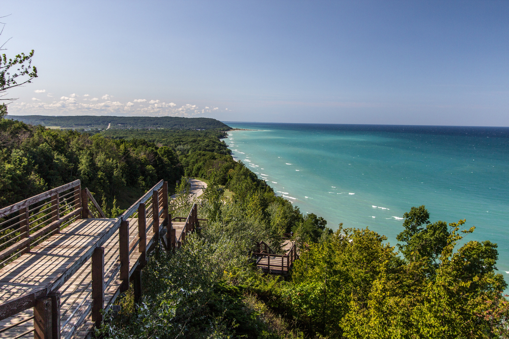 An overlook of Lake Michigan. The water is calm and very blue. All around the overlook are trees with green leaves and there is a boardwalk where you can see the lake from different angles. The lake goes on for miles in the distance.