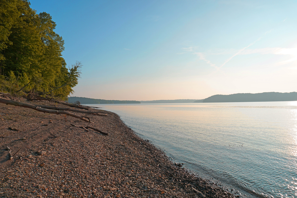 The rocky shore of Lake Monroe. The lake is calm and there are some trees on the shore. In the distance you can see other bits of land.