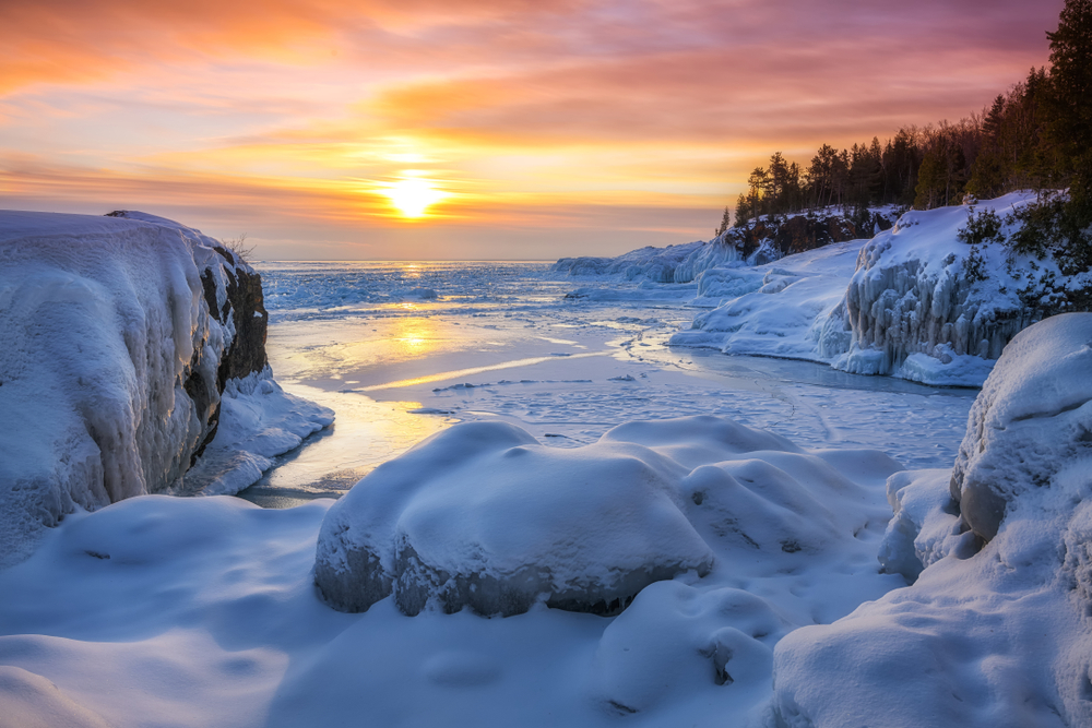 A rocky beach on Lake Superior in the winter. The beach and rocks are completely covered in snow and ice and the trees nearby have no leaves. The sun is setting so the sky is yellow, orange, and pink.