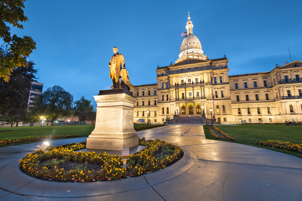 A sculpture of a man lit up outside of the lit up state capitol building in Lansing Michigan. The building is a greek revival style and has a large green lawn, a walk way, and flower beds with yellow flowers around it and the sculpture.