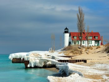 A small white light and black light house with red shingles on the roof. It is on the sandy shores of a lake but there is also snow and ice hanging off the dock near the lighthouse. There are dunes with dried grass and trees with no leaves. One of the best things to do in Michigan
