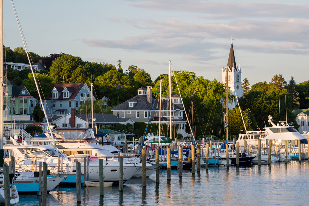 A view of the harbor on Mackinac Island. There are lots of sail boats and large buildings near the harbor. You can see a church steeple behind some trees. It is one of the best things to do in Michigan.
