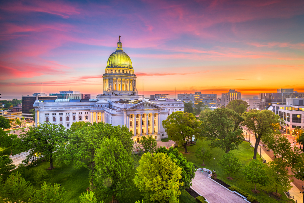 A slight aerial view of the Wisconsin Capital Building in Madison. It is a large Greek Revival building with a tall green dome in the middle. It is surrounded by a grassy park with trees. The building is lit up and the sun is setting so the sky is red, yellow, orange, pink, and purple.