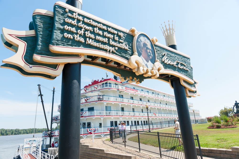 A sign with a portrait and quote from Mark Twain over a dock leading to a classic steam white and red steamboat on the Mississippi River. It is in Mark Twain's hometown.