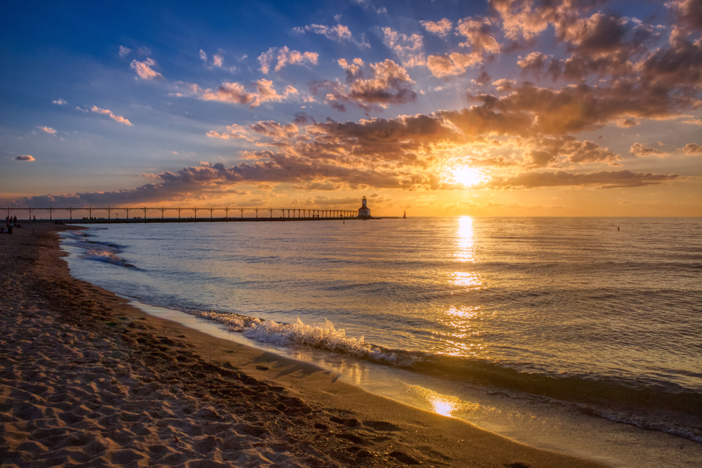 The beach in Michigan City at sunset. You can see a sandy shore, the lake is calm, and there is a lighthouse that is connected to the shore in the distance. The sun is setting and the sky is blue, yellow, and orange.