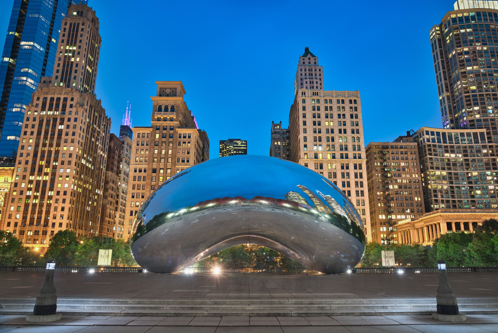 The famous silver bean sculpture in Millennium Park in Chicago. It is twilight and the sky is a dark blue. Behind the sculpture is the city skyline with the buildings all lit up. You can see the sky and buildings reflected in the sculptures surface.