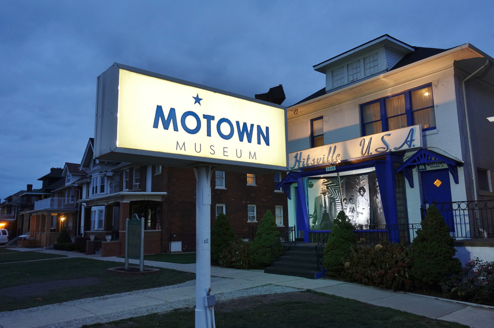 The exterior of the Motown Museum. It is a small house with blue trimmings and a door. There is an illuminated sign in the yard with blue lettering that says 'Motown Museum' and a sign on the building says 'Hitsville USA'. One of the best things to do in Michigan.