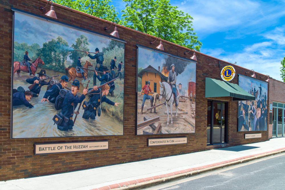 A brick building with three painted murals on the side of it. The murals depict different scenes like a battle scene and a man riding a horse. A great stop on any Missouri road trips