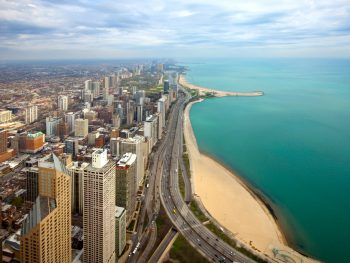 An aerial view of the Oak Street Beach in Chicago. You can see the beach on Lake Michigan and then right behind it is the city skyline of Chicago. The beach and the city extend into the horizon for miles and the water on the lake is very blue. It is one of the best things to do in Illinois