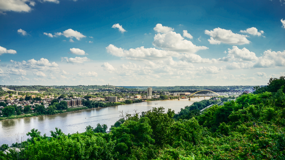 A view of the Ohio River. On one side of the river there is a large city and you can see a bridge in the distance. On the side of the river where the photo was taken you can see nothing but green trees.