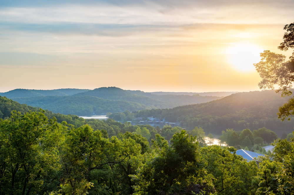 The view of the mountains in the Ozarks at sunset. The mountains are covered in green trees, you can see some water, and the roofs of some buildings.