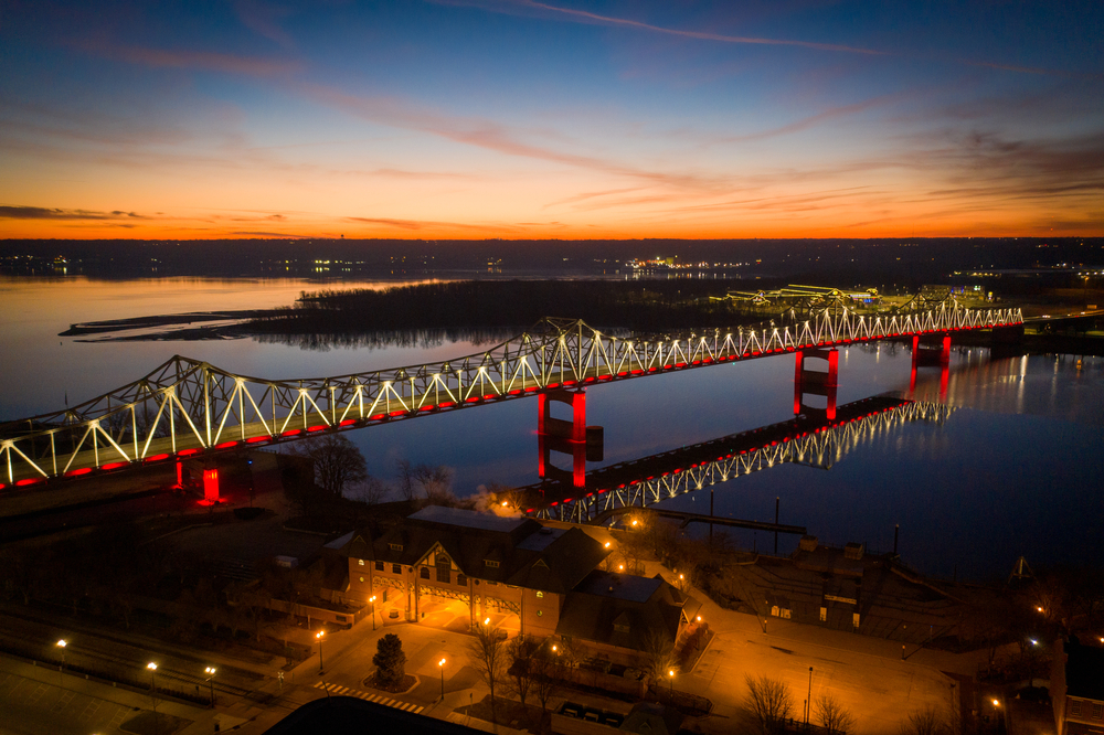 A large bridge going over the river in Peoria Illinois. It is twilight so the sky is dark and orange, yellow, and blue. The bridge is lit up with white and red lights and in the distance you can see city lights on the shore of the river.