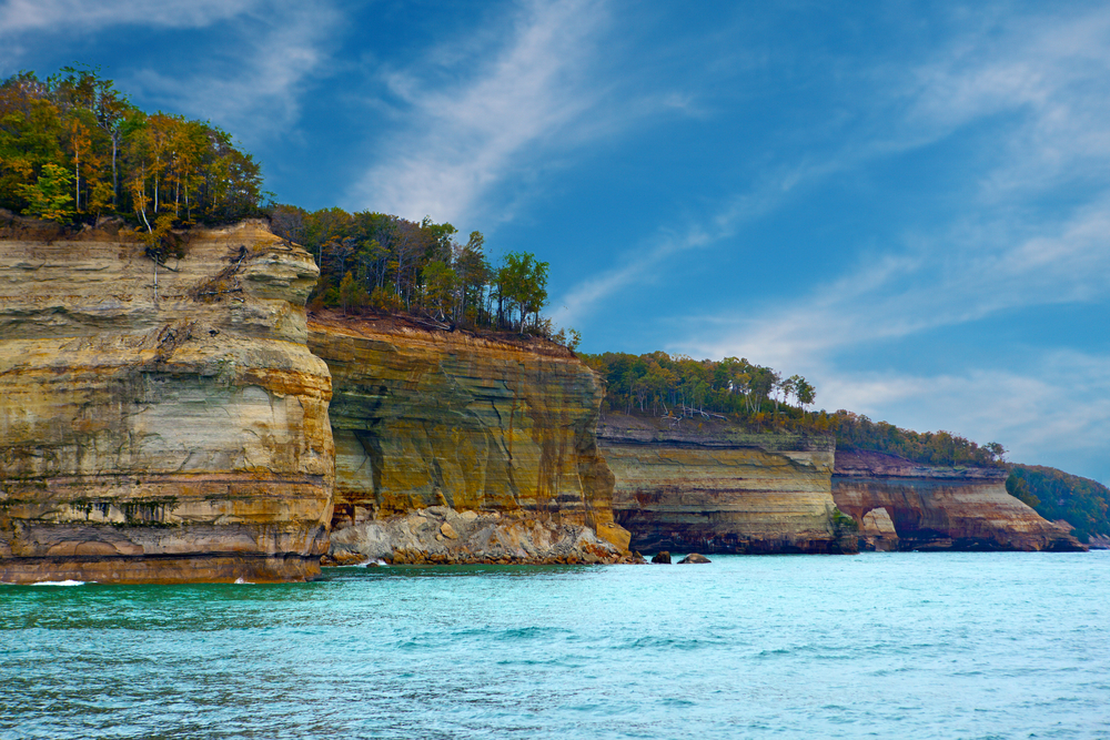 The rocky shore on the pictured lakes national lakeshore. The rocks are very colorful and there are trees growing on them. The water and the sky are very blue and calm.