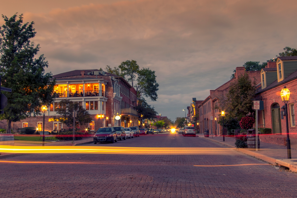 Looking down the street of St. Charles. It is twilight and the sky is dark and cloudy. The street lights are on and you can see one of the buildings lit up. There is a light trail going across the picture from a car driving by.