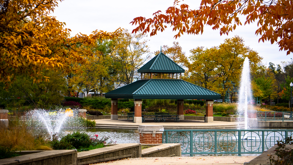A gazebo next to a large pond with water fountains on it in a park. The gazebo is made of brick and has a green roof. There is a green railing around the pond and you can see flower beds with pink and yellow flowers and tall grasses. There are trees around the park with green, yellow, and red leaves.