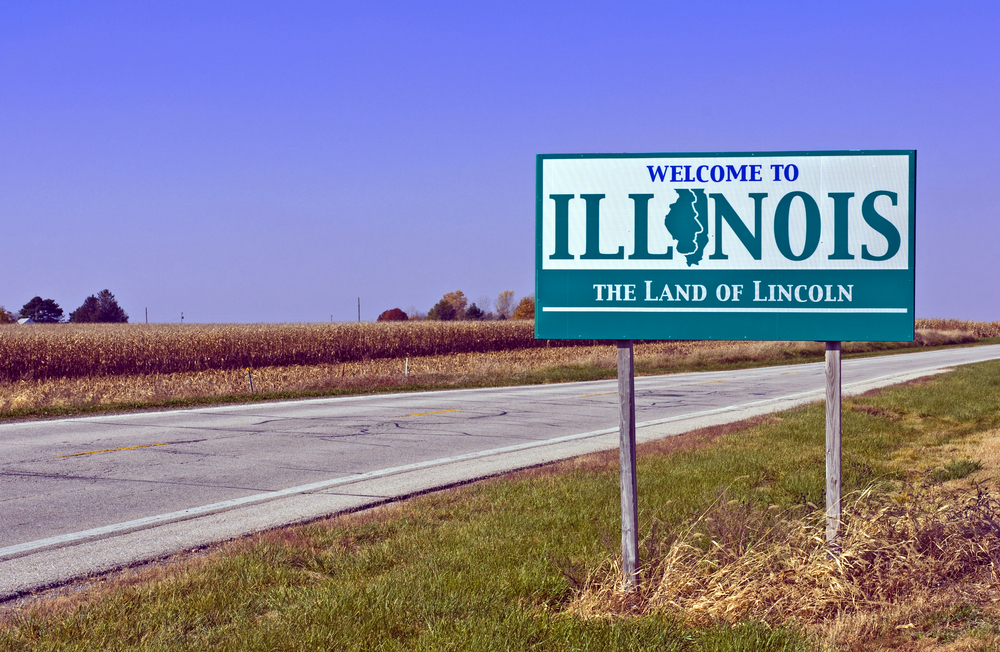 A sign on the side of the road welcoming you to Illinois. The road is surrounded by corn fields. The sign says 'Welcome to Illinois - The Land of Lincoln' in a teal blue and the second i in Illinois is the shape of the state.