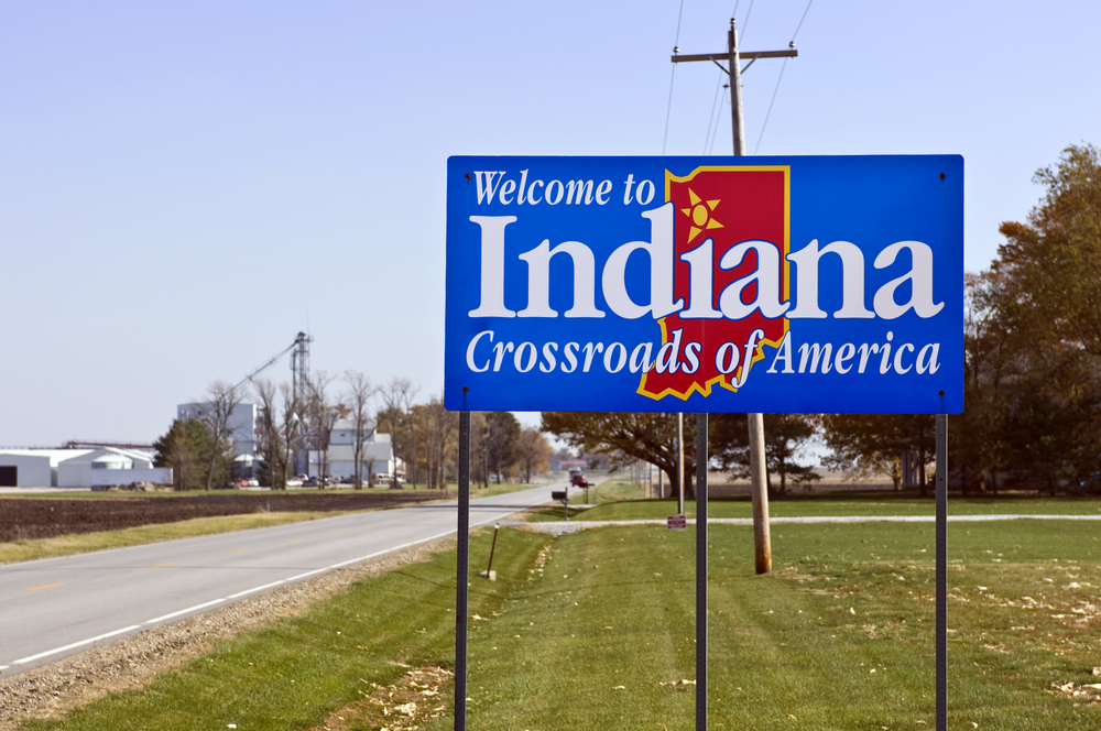 A blue sign welcoming you to Indiana that says 'Crossroads of America'. It is a blue sign with the shape of the state in red with a star over the second i in the word. One of the best things to do in Indiana