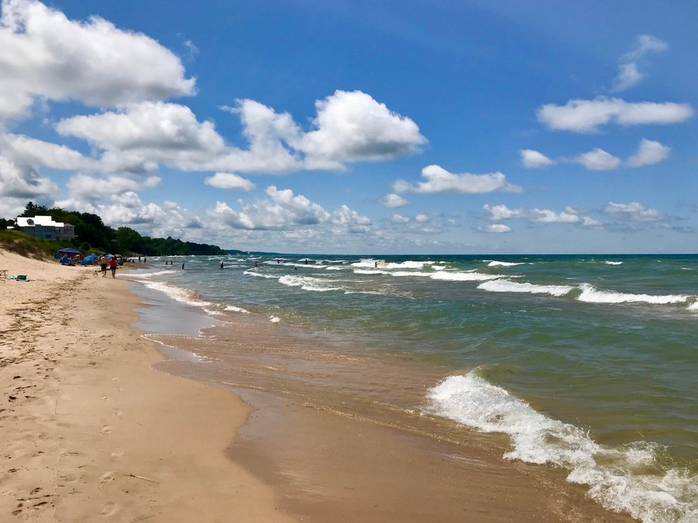 A sandy beach in South Haven Michigan. There are people swimming in the water and walking along the beach in the distance. The water is very blue and so is the sky.
