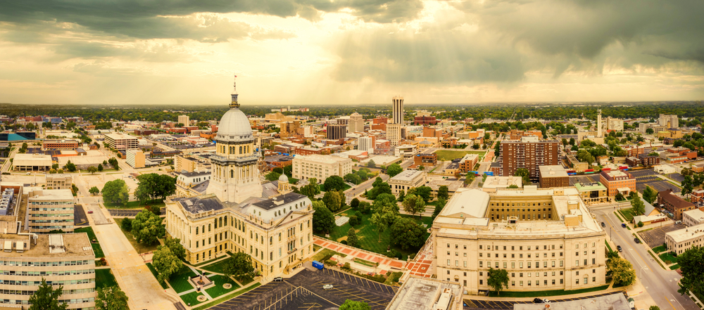 An aerial view of the city of Springfield on a cloudy day. There is sun shinning through some of the clouds. You can see the Capitol Building and more buildings and homes in the distance. There are trees scattered throughout the city.