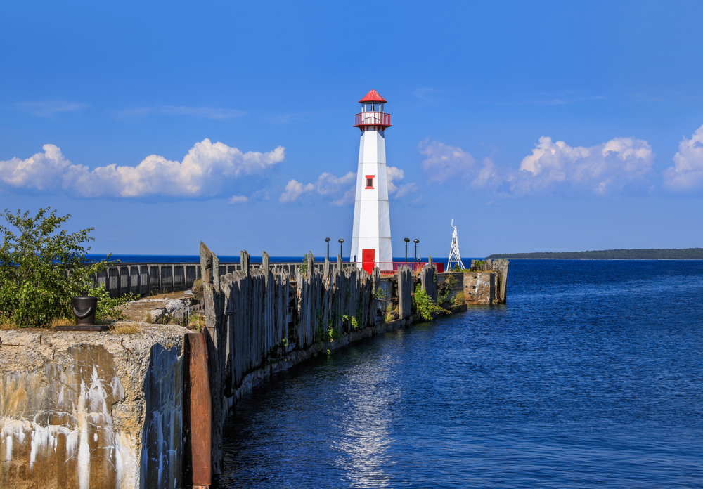 A small white lighthouse with red accents on the end of a small dock in the lake. The lake is calm and blue and the dock looks run down. The sky is very blue with a few clouds.
