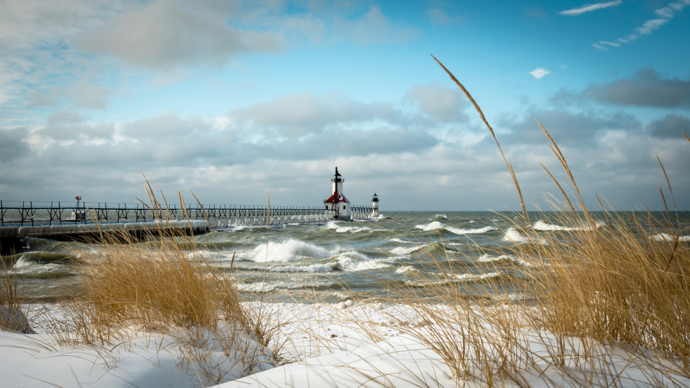 A view of the St. Joseph Lighthouse from the shore of the lake. There is snow on the shore and tall dried grass. You can see waves crashing in the lake.
