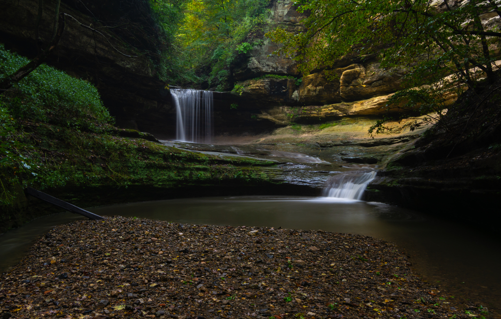 A waterfall at Starved Rock State Park, one of the best things to do in Illinois. It is a small bridal veil fall that runs into a small river and pond area. The fall is surrounded by rock formations covered in moss and trees with green leaves.