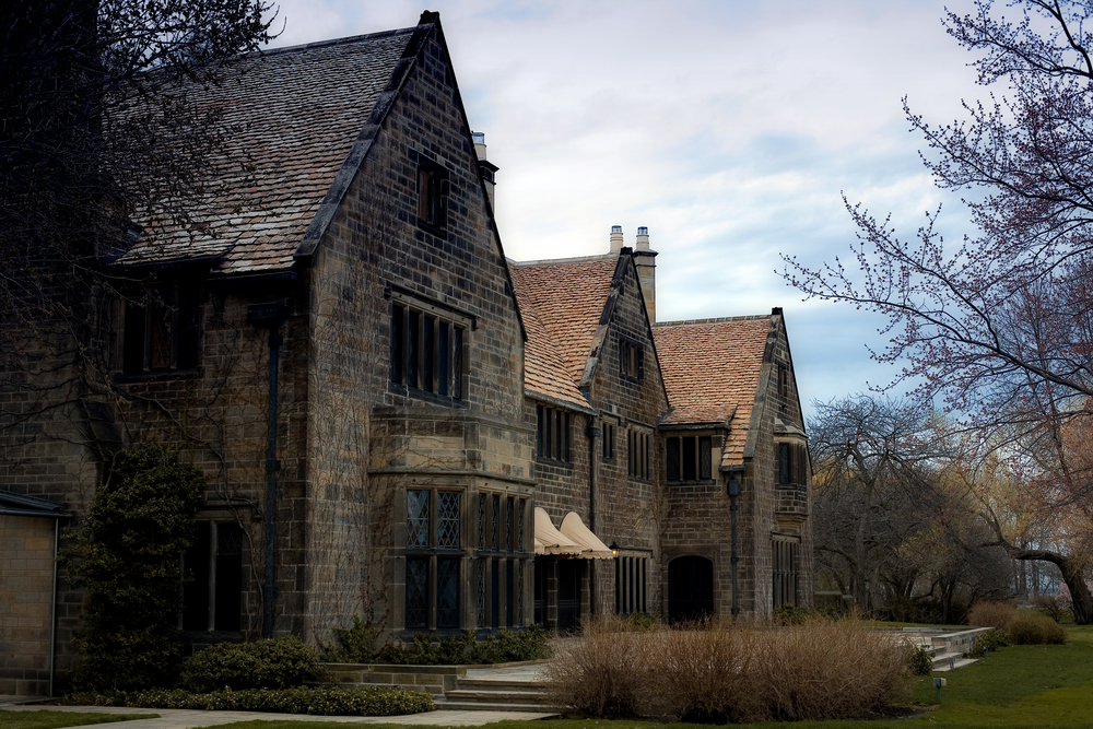 An old stone building at the Henry Ford museum complex. There are dead shrubs around it, the trees near it have no leaves, and there is a small patch of grass in front of it. It is an overcast day.