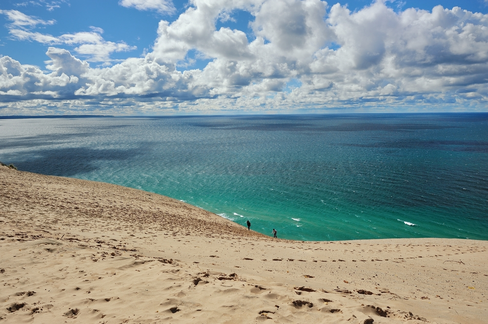 A huge sand dune leading done to crystal blue water with people walking along the shore. The Dune climb at Sleeping Bear Park one of the things to do in Traverse City