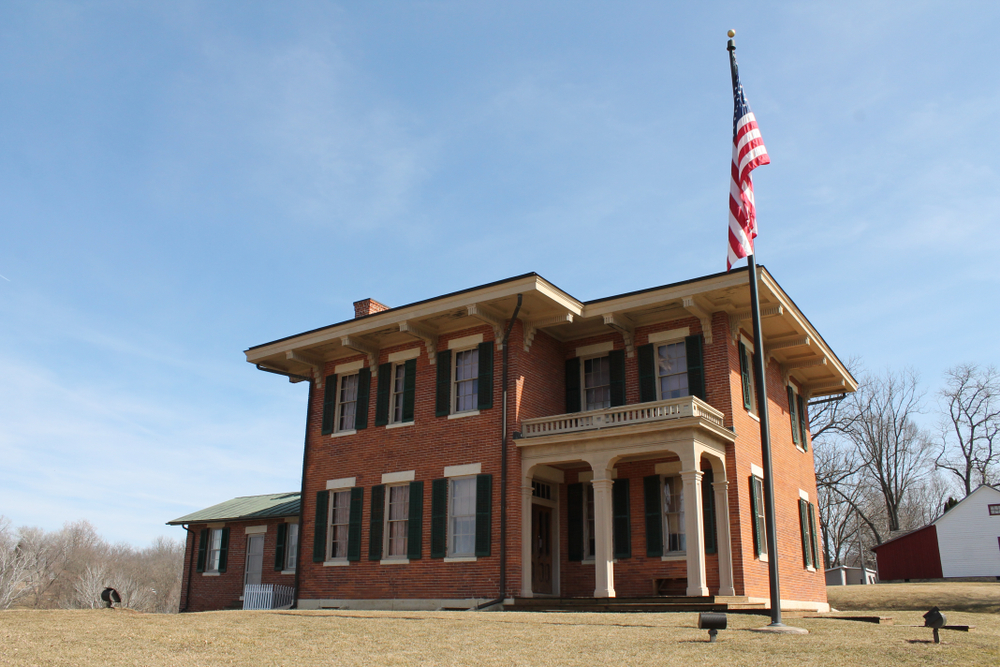The exterior of the Ulysess S. Grant Home National Historic Site. It is a brick house with two stories, lots of windows with black shutters, and a small covered porch by the front door. In front of the house there is an American flag on a pole. Around the house is a grassy area and behind it you can see another building and trees with no leaves.