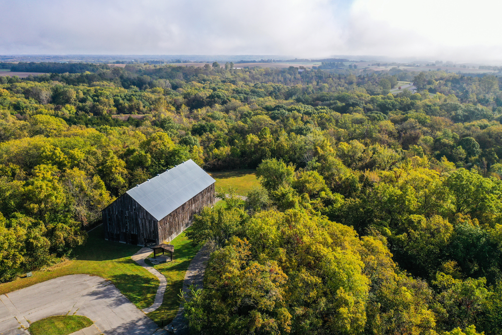 An aerial view of the Weston Bend State Park. It is covered in trees with green leaves, but in the far distance you can see fields. There is a restored barn at the front  of the image.
