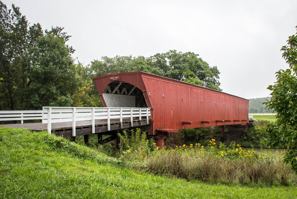 An old, red covered bridge in a country setting.