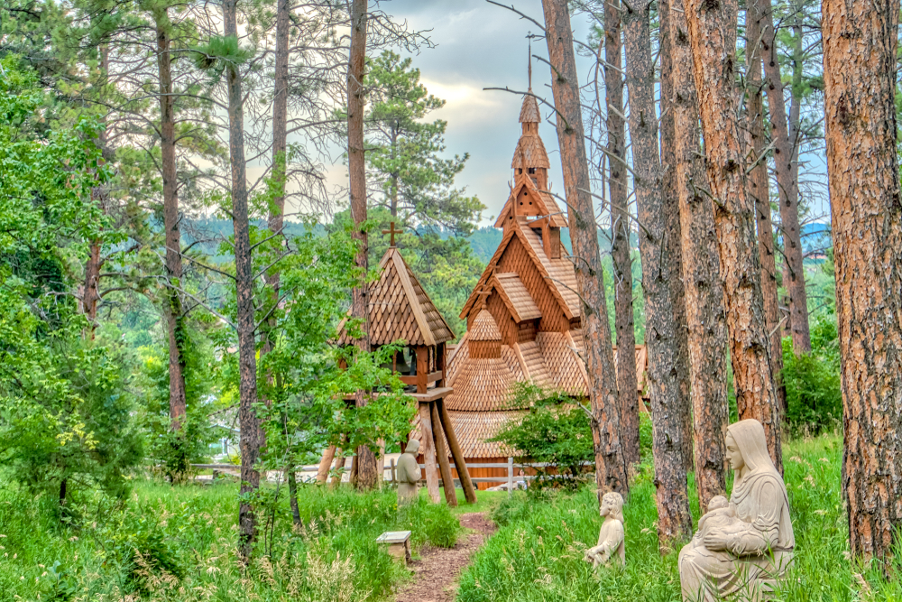 The Chapel in the Hills in Rapid City, South Dakota: wooden church nestled in forest. Religious statues in foreground.