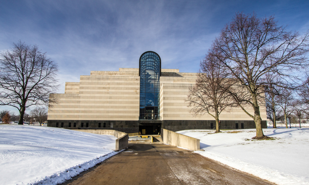 A concrete building with a glass atrium and snow around it. Visiting the History Museum is one of the things to do in Lansing MI