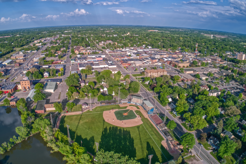 An aerial view of Alexandria Minnesota. You can see a baseball field, parks, buildings, and homes. There are large trees scattered throughout the city. One of the best things to do in Minnesota.
