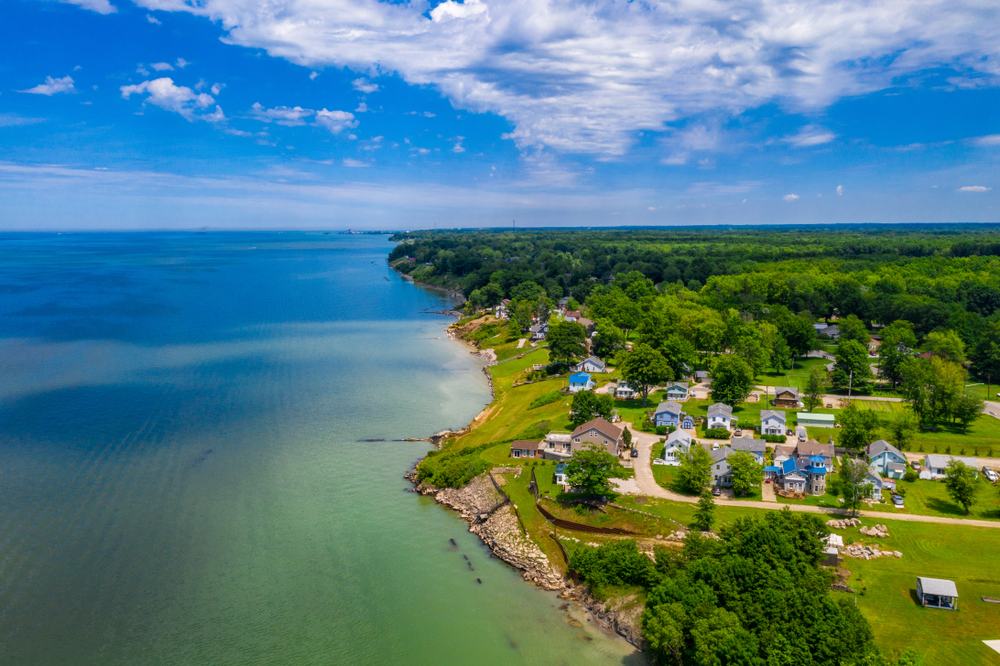 An aerial view of looking down the Lake Erie coast in Ashtabula. The water is very blue and the shoreline is mostly rocky or grassy. You can see a large area of trees and then some houses that are very close to the shore line, up a slight hill.