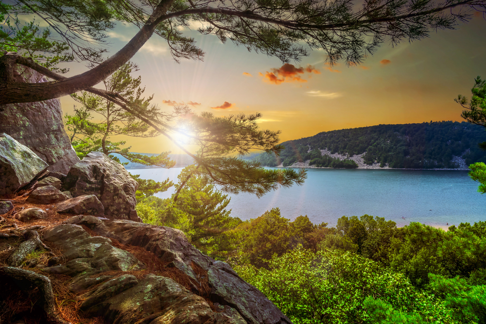 The view of Devil's Lake at Devil's Lake State Park in Baraboo. You can see a rocky cliff, trees with green leaves, a blue lake, and a hill on the other side of the lake covered in trees.