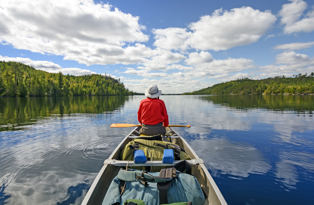 A person in a large kayak on a lake. They are wearing a red shirt and a hat. They are looking out into the distance. There are trees on either side of the lake.