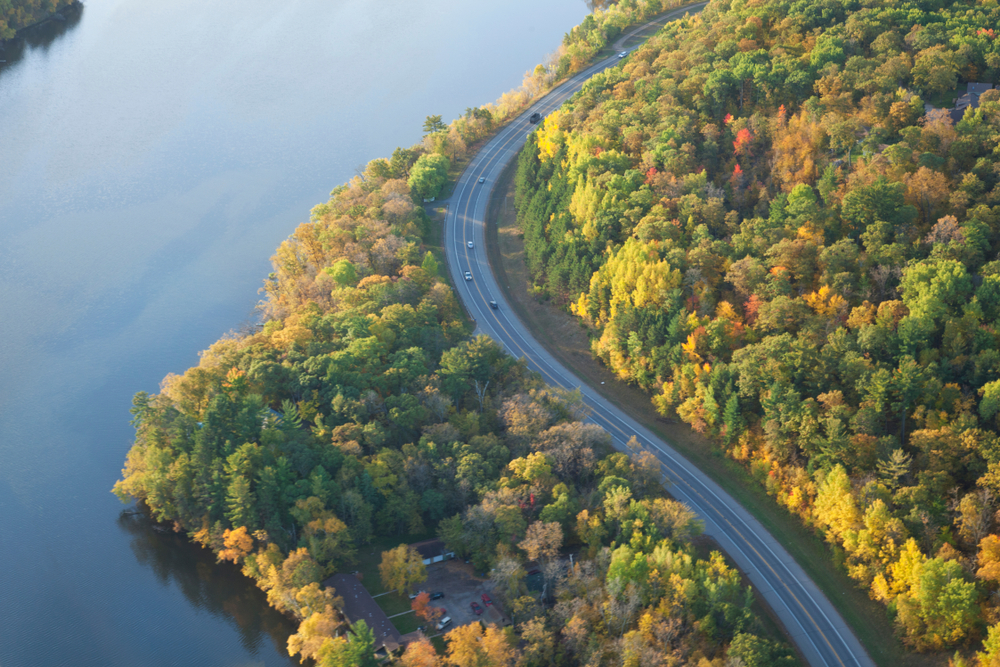 An aerial view of a twisting road near Brainerd. It is curving along the river and surrounded by trees. The trees have green, yellow, orange, and red leaves.