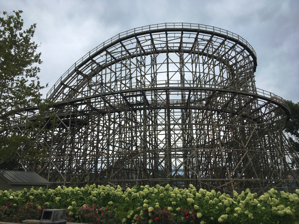 Looking at a wooden rollercoaster. The sky is dark and there are a few trees near the rollercoaster.