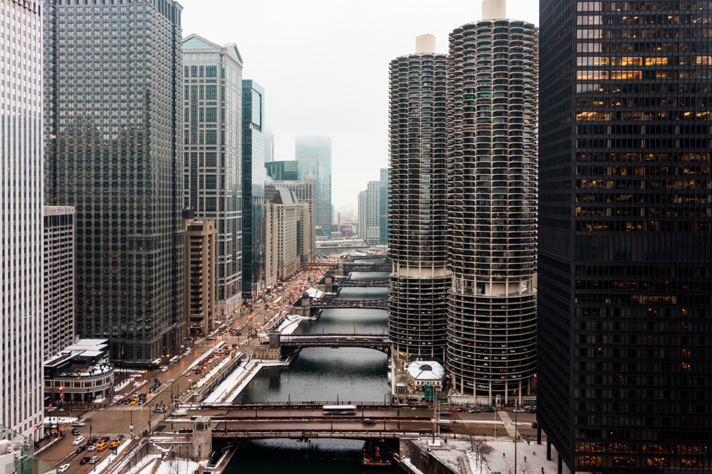 Looking down the Chicago River on a snowy winter day. There is snow on the ground and the river looks frozen. It is an overcast grey day.