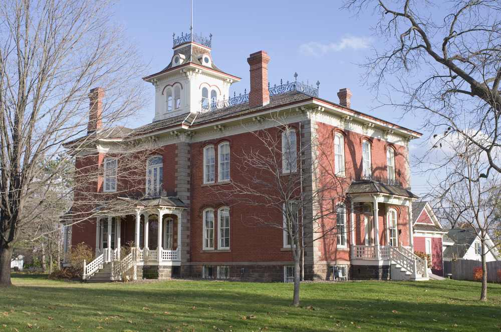 A large Victorian mansion in a Wisconsin small town. It is made of brick and has white trim. There are several staircases on it and a white section on the roof that resembles a bell tower. It has a large lawn with trees with no leaves.