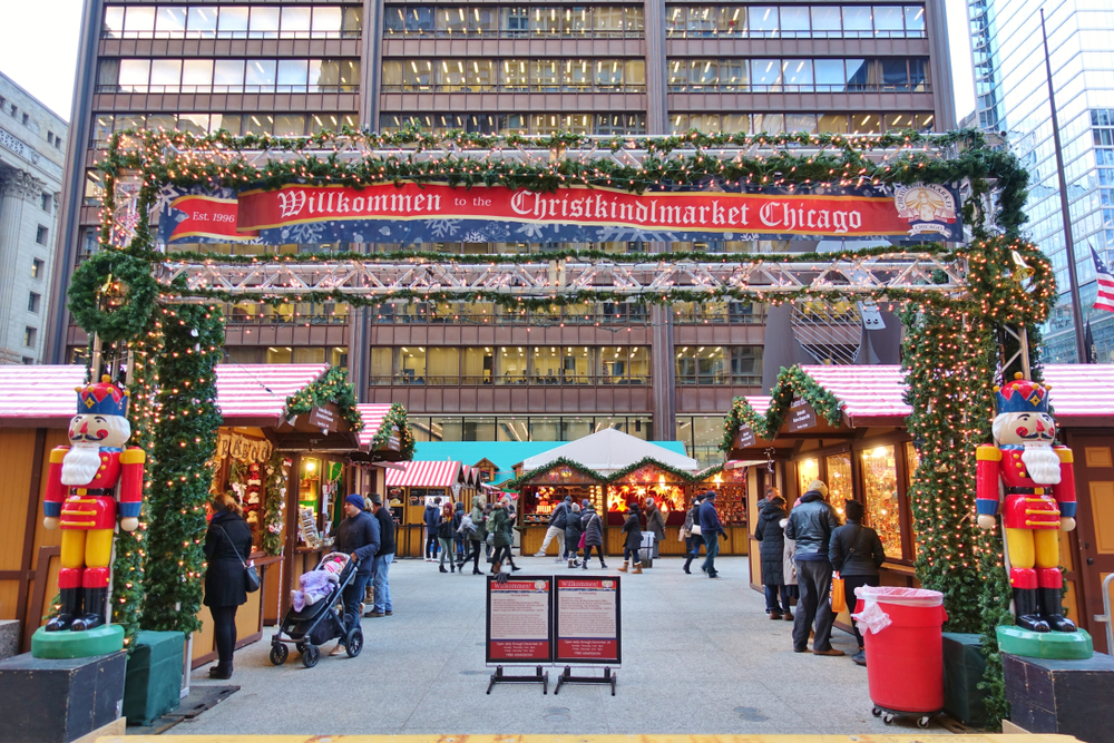 The front entrance of the Christkindlmarket in Chicago during the day. It is a large archway with a red sign on it. The arch way is covered in greenery and lights with two nutcrackers. Past the entry you can see small stalls of little Christmas hits all lit up.