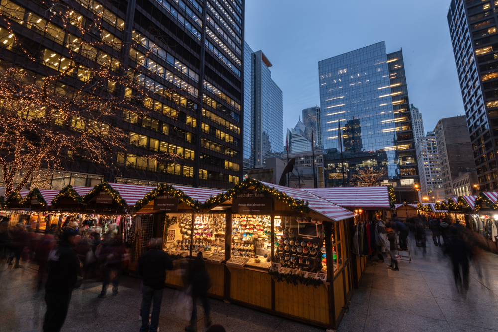 A Christmas market in downtown Chicago at Christmas time. It is twilight and the little shops are all lit up from inside. There are twinkle lights on them and on the trees in the park. One of the best things to do at Christmas in Chicago.