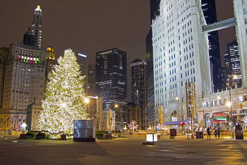 A large Christmas tree all lit up at night in Chicago's Millennium Park. There are people walking around, the shops are all lit up, and there are other trees with lights on them.