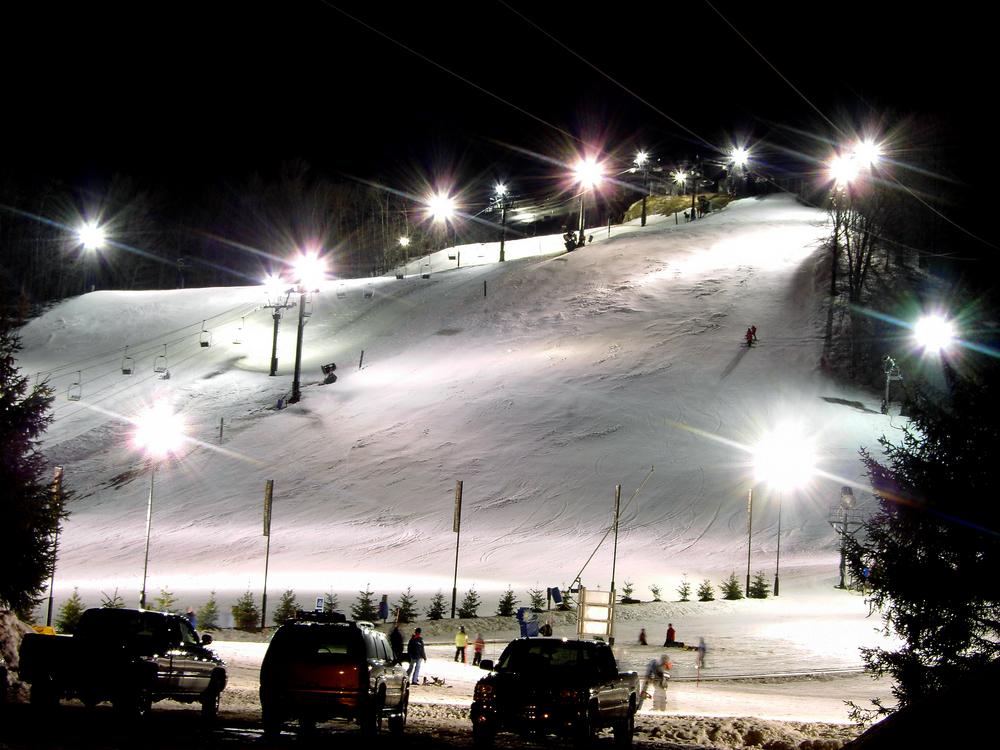 Illuminated Michigan ski resort with bright lights and packed snow