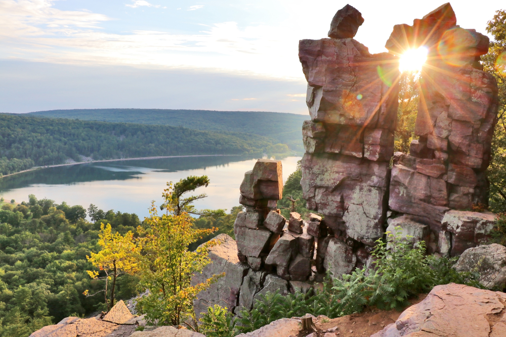 One of the unique rock formations at Devil's Lake State park. The sign is shinning between a slit in the rocks. You can see down into the valley where the lake is and there are hills covered in green trees. Dells of Wisconsin