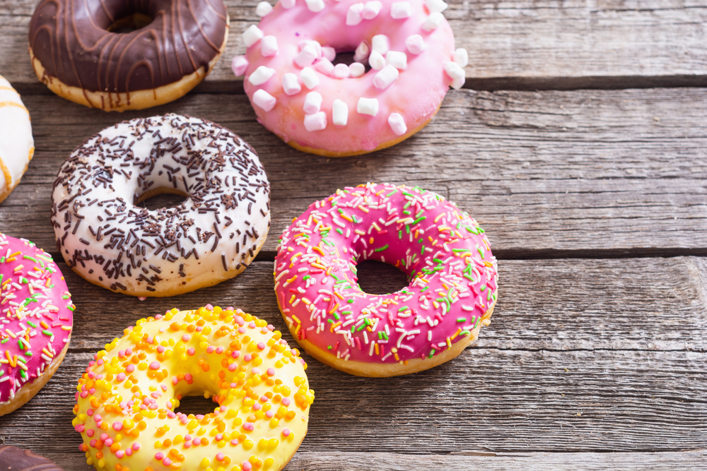 A collection of brightly decorated donuts. They are on a gray wood table. The donuts have red, white, yellow, and brown icing. They also have colorful sprinkles, brown sprinkles, and mini marshmallows.